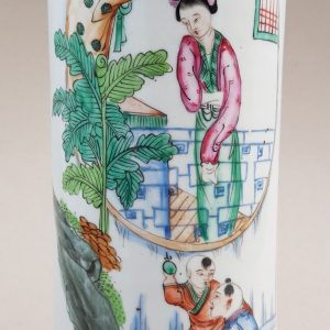 An antique Chinese famille rose porcelain hat stand painted with a lady watching two child playing